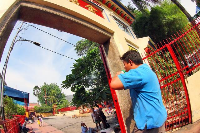 Seorang pemuda keturuan Tionghoa memasuki gerbang Vihara Dharma Bakti. Cuaca yang panas, dia menyegarkan dengan minuman yang dingin. Di depannya nampak para pengemis yang sedang berteduh di bawah pohon (dok.pri).